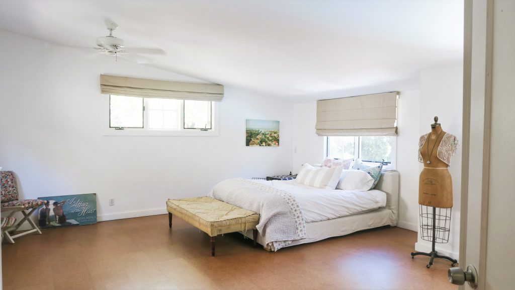 rustic modern bedroom white bedroom neutral slipcover bed board cork flooring