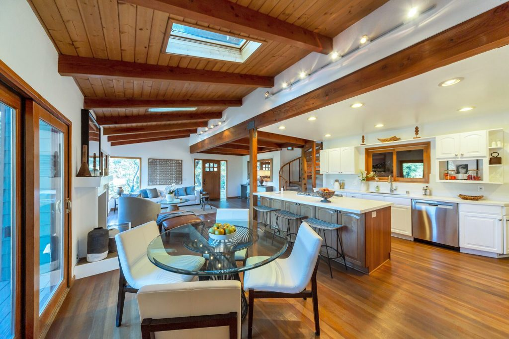 Open living room dining room kitchen wood beams and wood floor