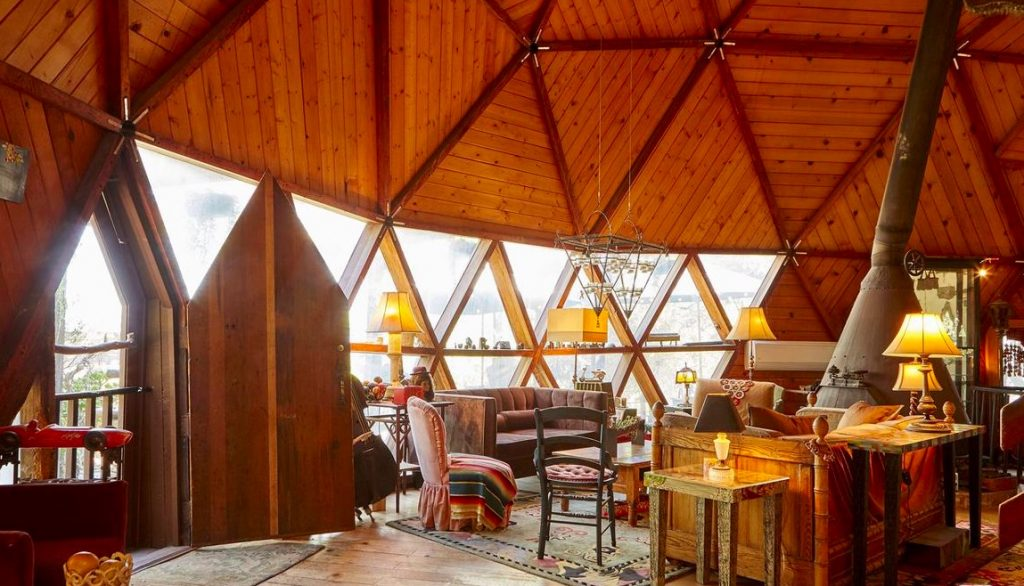wood home dome house triangular windows and doors round house seventies style center of room fireplace.