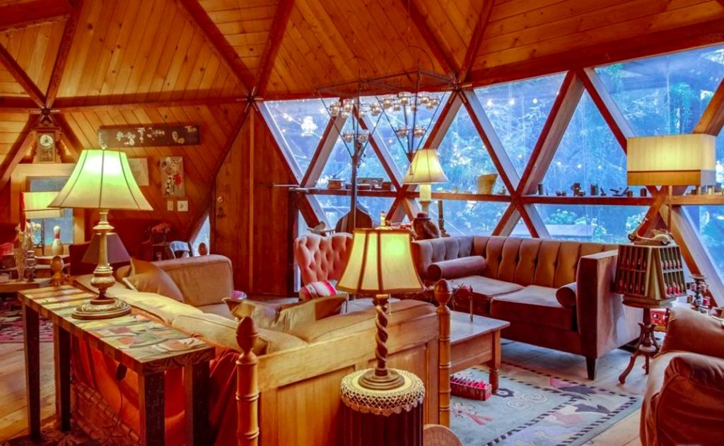 wood home dome house triangular windows and doors round house seventies style center of room fireplace lamps indian rug velvet couch