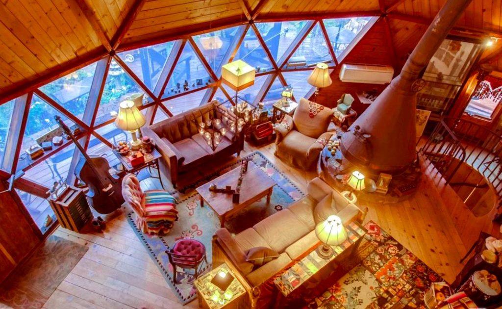 Circular home wood floors wood walls  wood triangular windows rustic rugs rustic lamps rustic furniture large metal wood burning stove rustic lamps