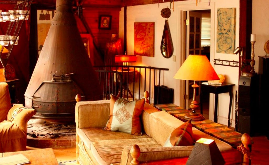 Dome house topanga canyon living room rustic couch amber light lamp long wood table large steal fireplace