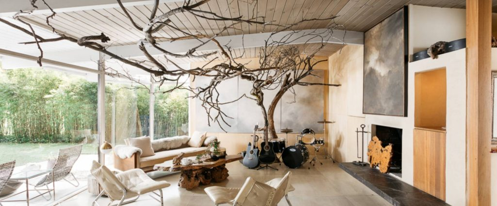 Outdoor room cozy cream lounge chairs sliced trunk wood coffee table driftwood wall and ceiling fixtures large nature art prints outdoor fireplace