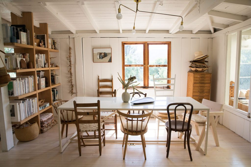 white dining table with mix and match chairs rustic modern bookcase