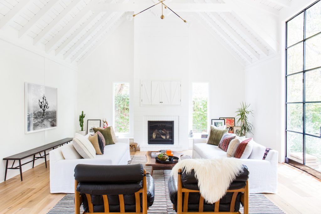 White walls white ceiling white fireplace white couch large windows leather chairs wood floors modern art minimal plants long wall bench
