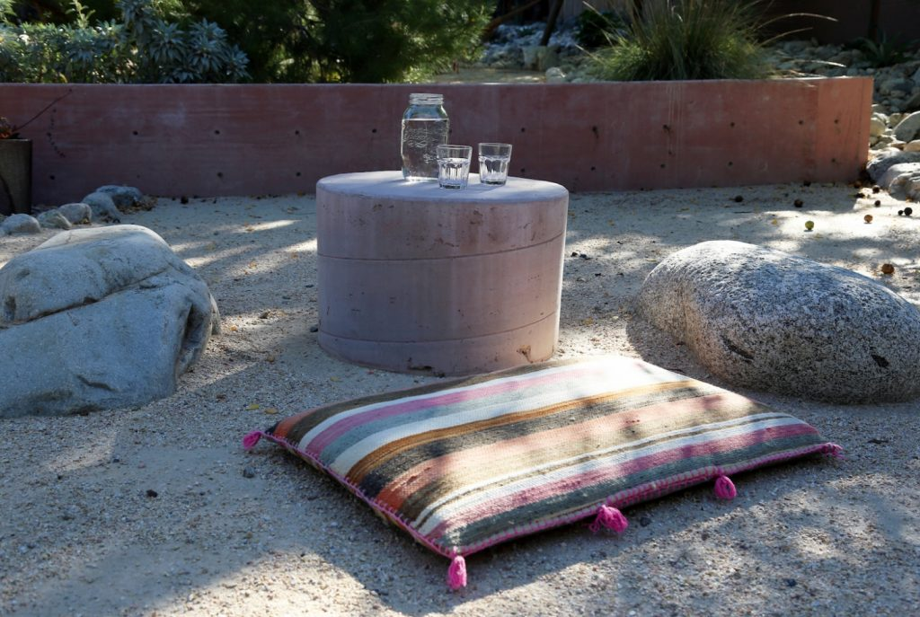rock sitting area outdoor cushions and a block table