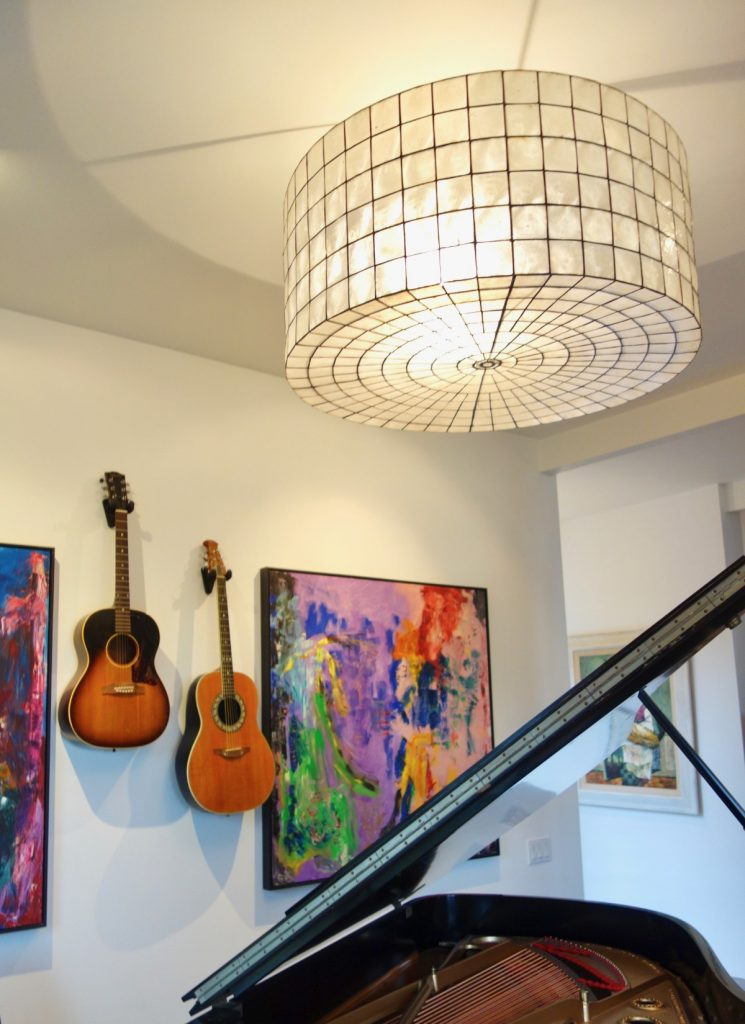 guitars hanging on wall with abstract art