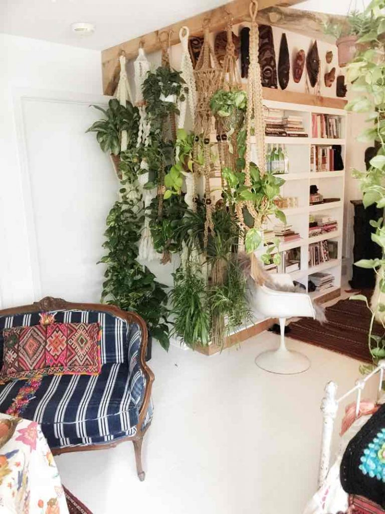 Floor to ceiling hanging plants create a room divider that is a boho modern hippie way to make more room for plants!